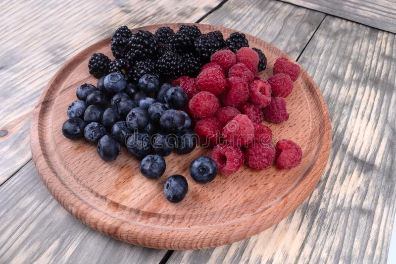 A set of blackberries, blueberries and raspberries laying on a wooden plate. Set of three groups of red, black and blue berries laying in a wooden plate standing stock photos