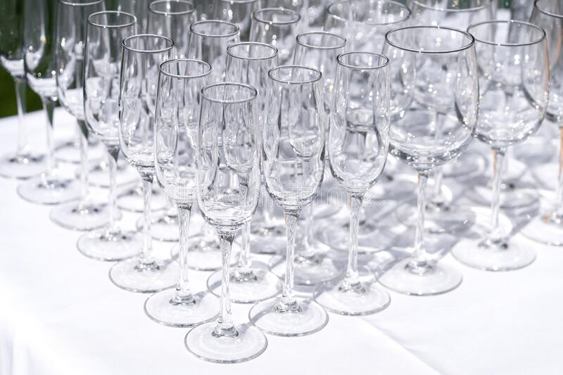 Set of blank empty wine glasses displayed in rows. Preparation for the holiday stock photo