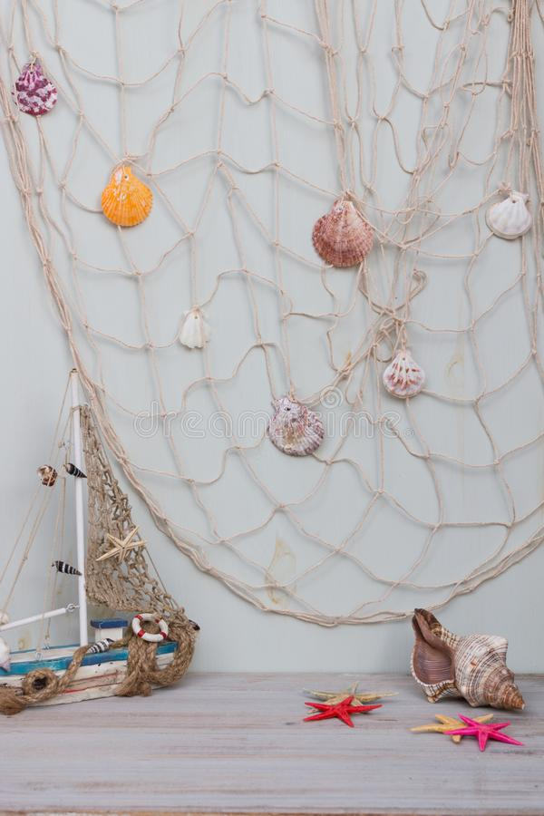 Set of boat, fishing net, starfish and seashells stand on light gray background. stock photography