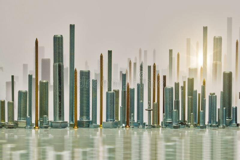Set of bolts resembling skyscrapers. A set of bolts arranged to resemble modern skyscrapers with a setting sun in the background royalty free stock image