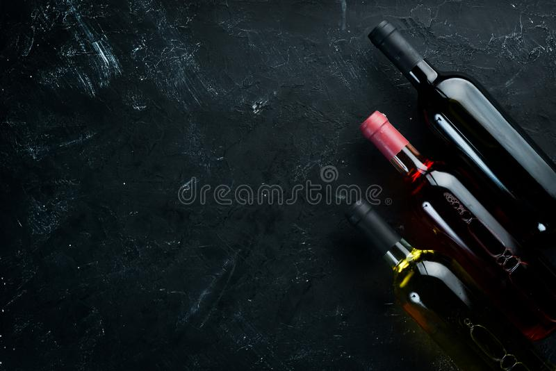 Set A bottle of white wine, red and rose wine on a black stone background. royalty free stock image