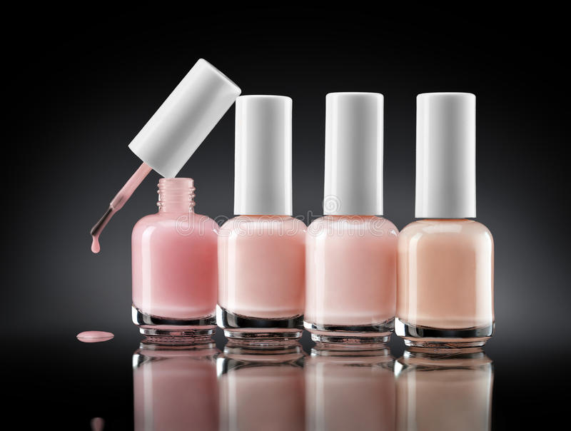 Set of bottles pearl colors nail polish on dark background. royalty free stock photos