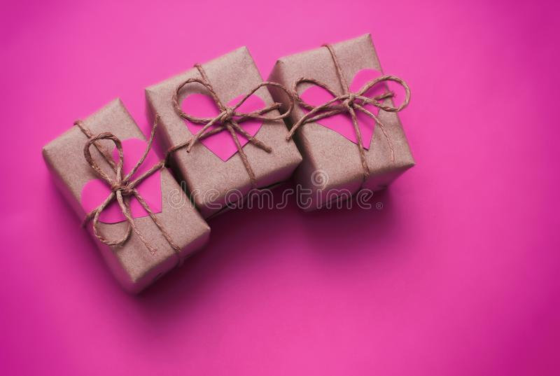 Set of brown gift boxes. Wrapped in craft paper and tied by hemp cord. Bright pink background and carton hearts decorative card. stock photography