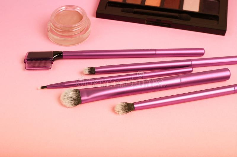 Set of brushes for makeup scattered chaotically on pink background. Professional makeup brushes and tools, make-up products set royalty free stock photo