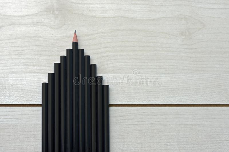 Set of building-shaped pencils on textured wooden plank. Set of pencils in the form of building, concept of educate to build stock photography