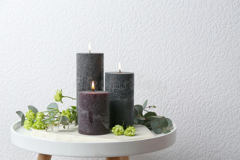 Set of burning candles, flowers and green branches on table at white wall. Space for text royalty free stock photography