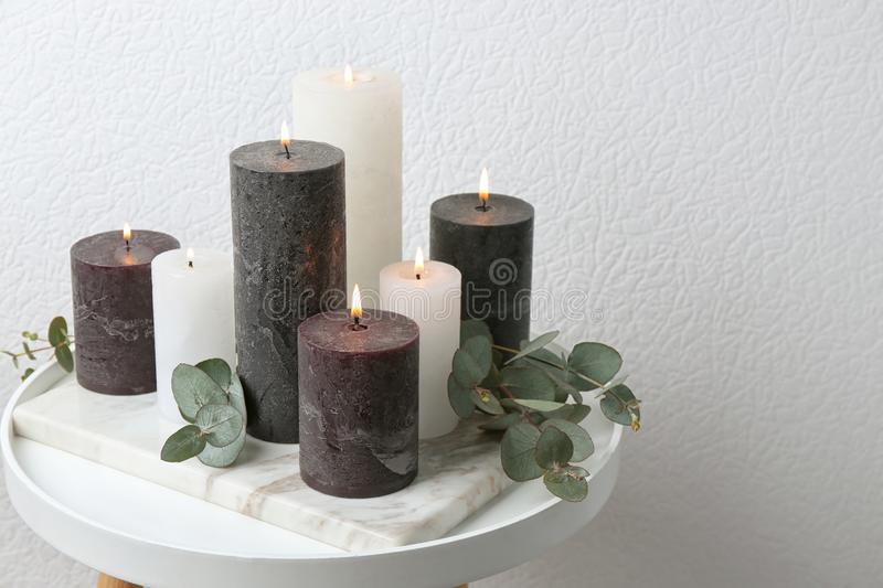 Set of burning candles and green branches at white wall, space for text. Set of burning candles and green branches on table at white wall, space for text stock photos