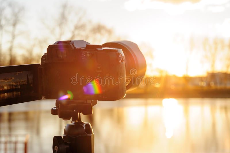 Set the camera on a tripod to record time-lapse video of the sunset.  stock photography