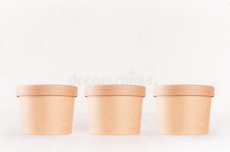 Set of cardboard package for different fast food for advertising, menu, banding identity - three round containers on white wooden royalty free stock photo