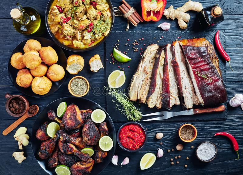 Set of caribbean dishes on a table. Set of caribbean dishes, jerk pork belly, chicken curry, fried dumplings, roasted chicken thighs and drumsticks on plates on royalty free stock photo