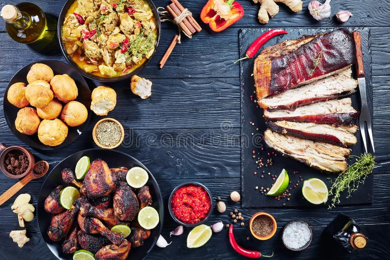 Set of caribbean dishes on a table. Set of caribbean dishes, jerk pork belly, chicken curry, fried dumplings, roasted chicken thighs and drumsticks on plates on royalty free stock images