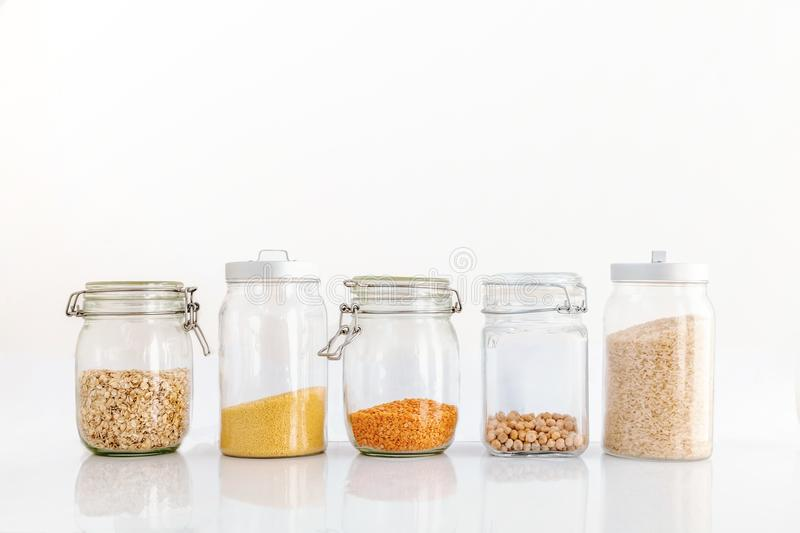 Set of cereals in a glass jar on a white background, rice chickpeas lentil oats millet healthy food and diet concept stock images
