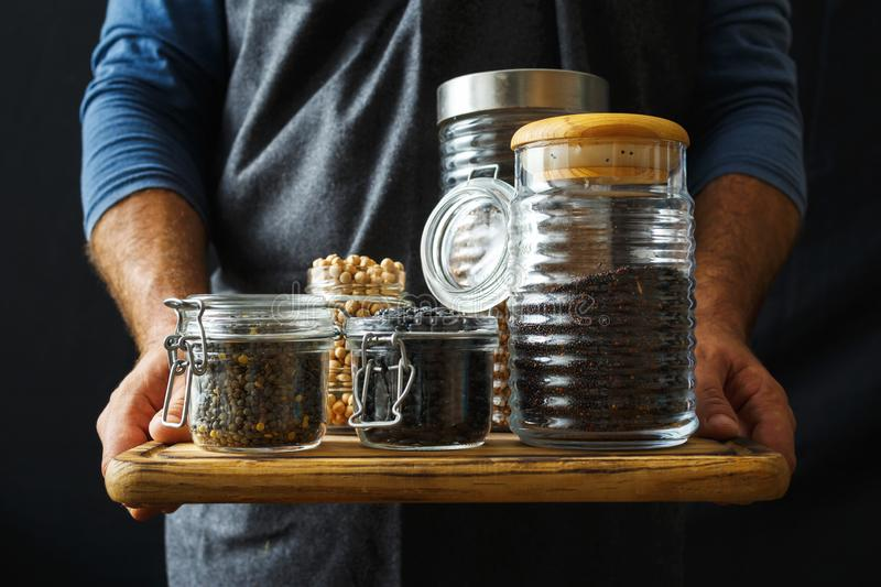 Set cereals seeds glass jars hands man Healthy food. Set cereals and seeds in glass jars in hands man. Healthy food stock photography
