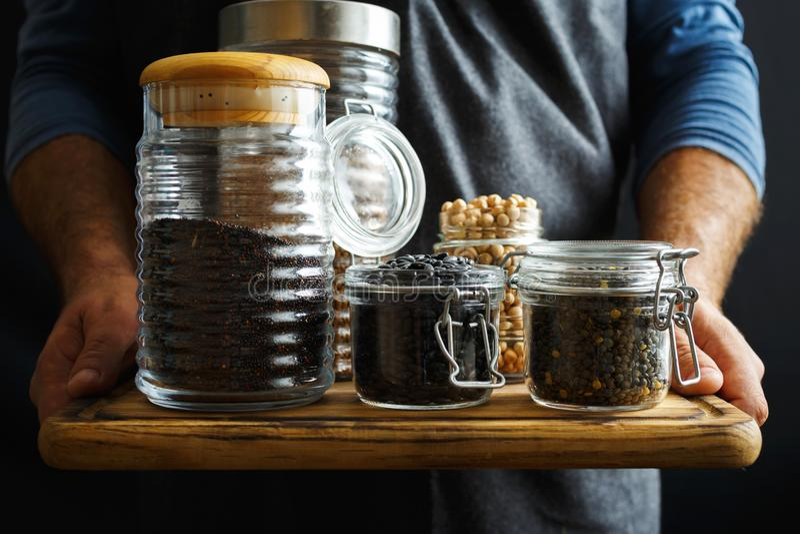 Set cereals seeds glass jars hands man Healthy food source protein vegetarians. Set of cereals and seeds in glass jars in hands man. Healthy food, source of royalty free stock images