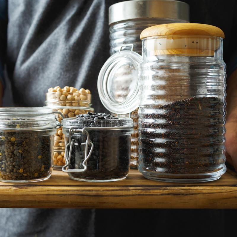 Set cereals seeds glass jars hands man Healthy food source protein vegetarians. Set cereals and seeds in glass jars in hands man. Healthy food, source of protein royalty free stock photos