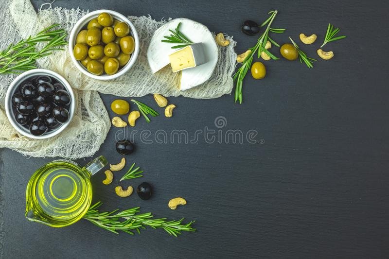 Set of cheese camembert, black and green olives, quail eggs, olive oil and rosemary. Set of cheese camembert, black and green olives, quail eggs on plates, olive stock image