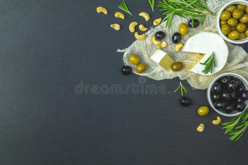 Set of cheese camembert, black and green olives, quail eggs, olive oil and rosemary. Set of cheese camembert, black and green olives, quail eggs on plates, olive stock photography