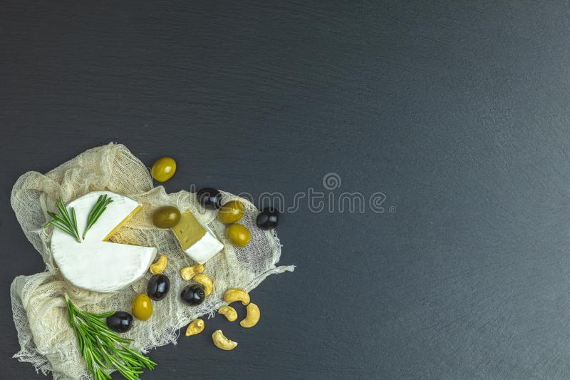 Cheese camembert, black and green olives, quail eggs, rosemary. Set of cheese camembert, black and green olives, quail eggs, rosemary, cashew nuts, on black royalty free stock photography
