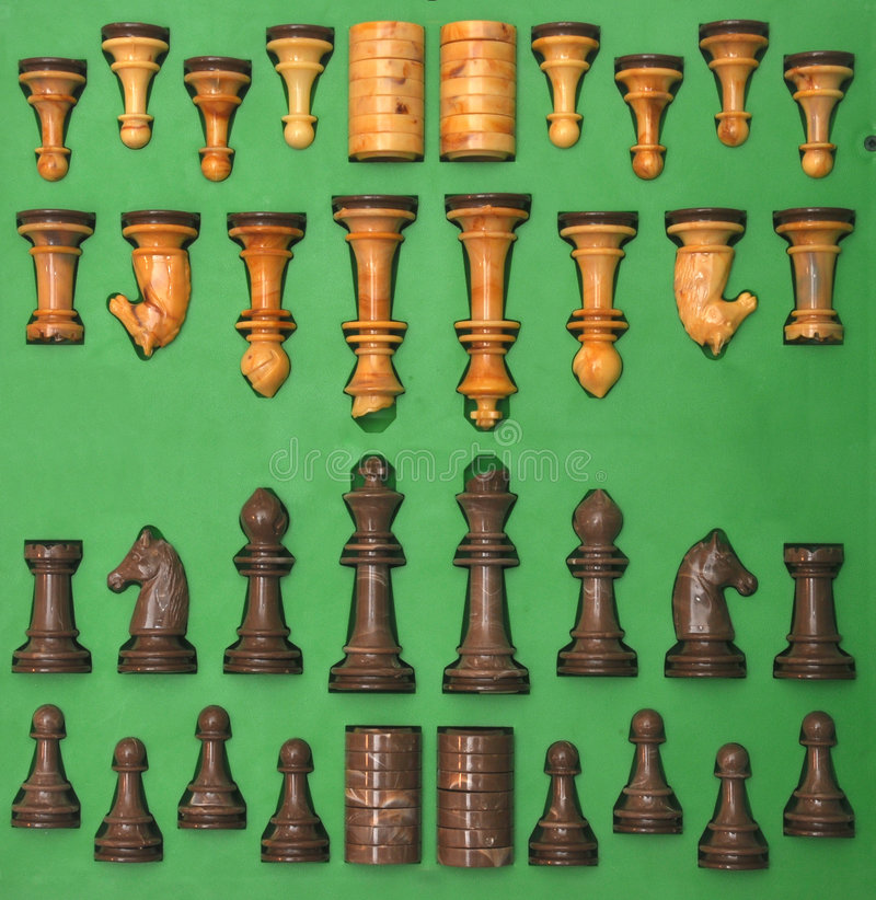 Set of chess pieces. Overview of set of white and black chess pieces on green background stock photos