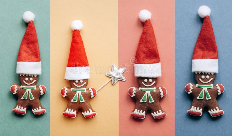 Set of Christmas gingerbread in the form of little ginger men in a red hat. On colorful backgrounds. Christmas or New Year concept in minimal style. Minimalism stock photo