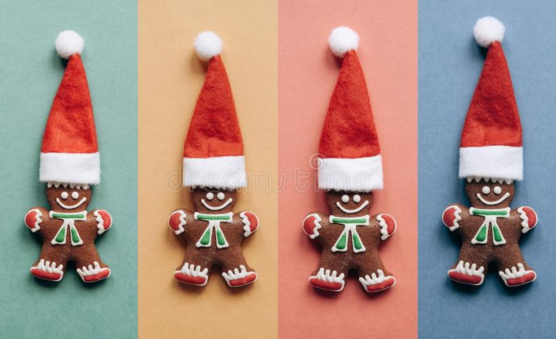 Set of Christmas gingerbread in the form of little ginger men in a red hat. On colorful backgrounds. Christmas or New Year concept in minimal style. Minimalism royalty free stock photography