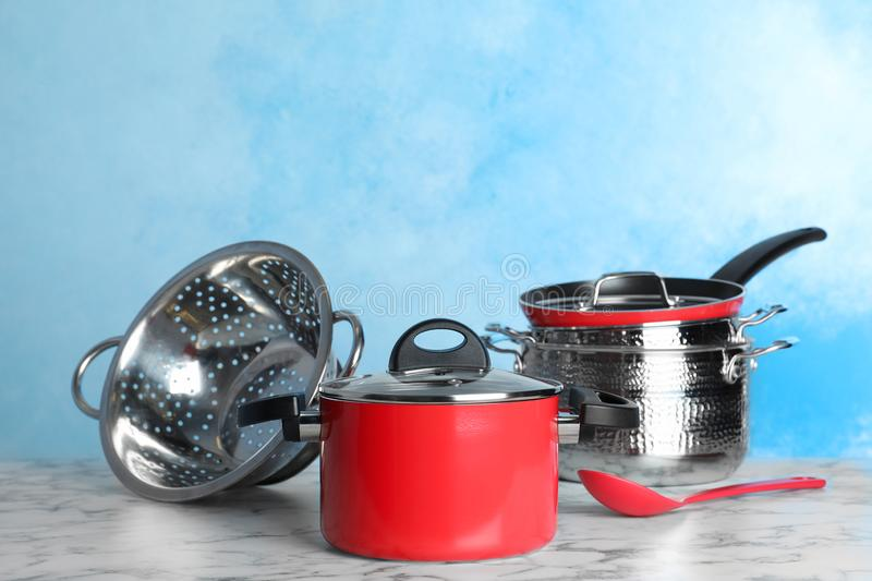 Set of clean cookware on table against color background. royalty free stock photography