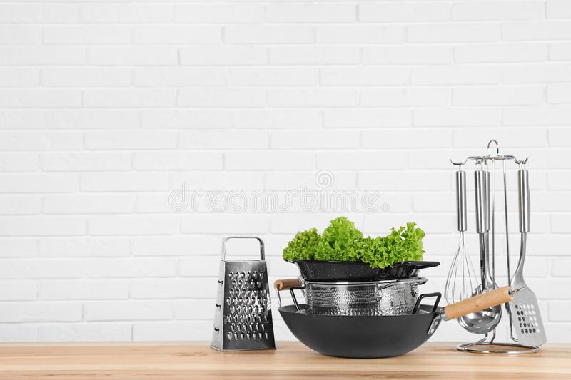 Set of clean cookware, utensils and lettuce on table against white brick wall. Space for text stock photos