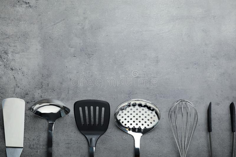 Set of clean kitchen utensils on grey background, flat lay. Space for text stock photos