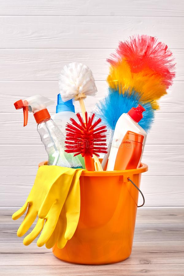 Set of cleaning supplies in colorful bucket. House cleaning items in bucket on wooden background. Cleaning service equipment royalty free stock images