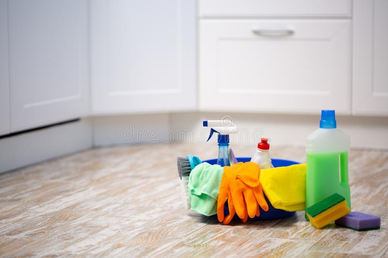 Set of cleaning supplies on floor in kitchen. Space for text royalty free stock photos