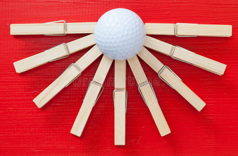 Set of cloth pegs and golf ball on wooden red desk stock images