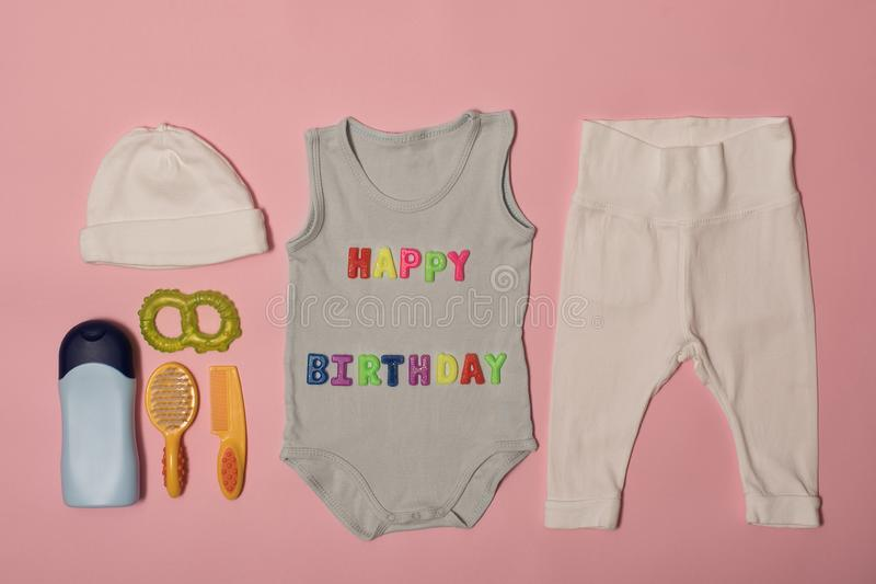 Set of clothes and accessories for newborn. Colored inscription happy birthday on a pink background royalty free stock image
