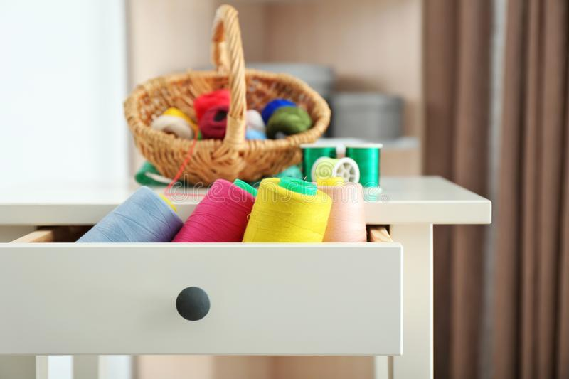 Set of color sewing threads in drawer of small table. Indoors stock photos