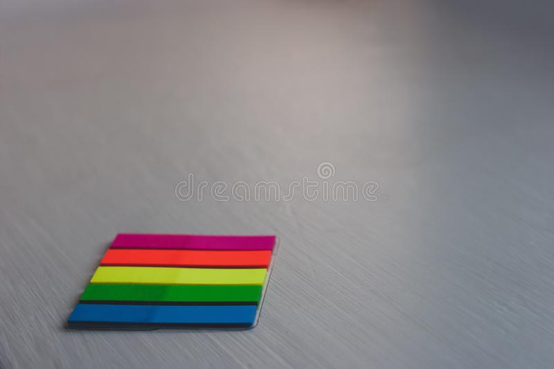 A set of colored bookmarks lies on a light colored surface from the bottom left. Stripe stickers. Red, yellow, green, blue. Selective focus, blurred background royalty free stock images