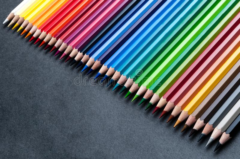 Set of colored pencils on dark. Set of colored watercolor wooden pencils, professional palette royalty free stock photo