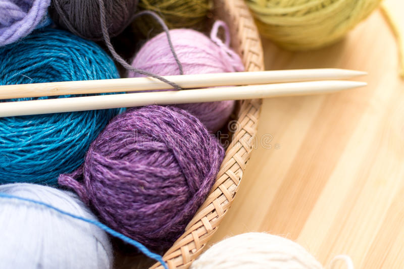 Set of colored yarn balls and needles on straw plate close up. Wooden table as a background royalty free stock photos