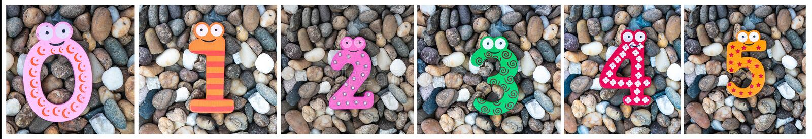 Set of colorful arabic wooden numbers 0-5 placed on pebbles pattern or small stones background in garden. Concept of number.  stock photography