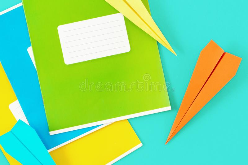 Set colorful exercise books paper airplane blue background Top v. Set of colorful exercise books with paper airplane on blue background. Top view minimalist stock photos