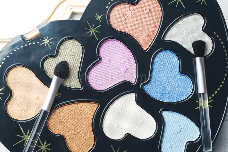 A set of colorful eye shadows and cosmetic brushes. Selective focus stock image