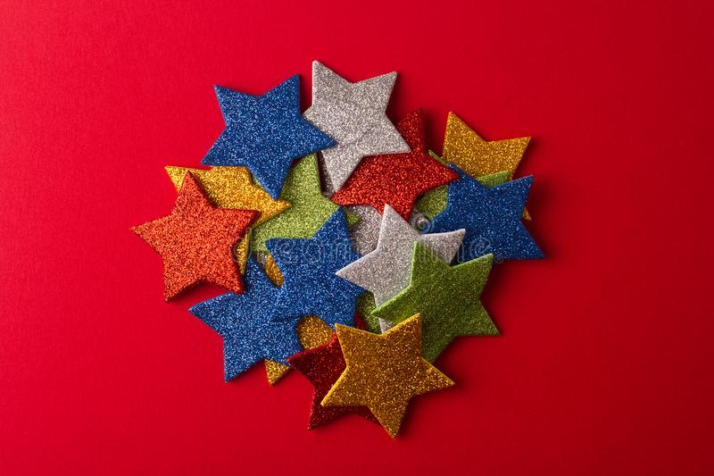 Set of glittering stars on red background. Set of colorful glittering stars on top of each other on red background royalty free stock image