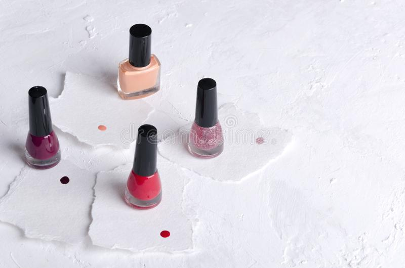 Set of colorful nail polish, samples of different colors on the pieces of paper.Empty space for text. Set of glass bottles of nail polish on the pieces of stock images
