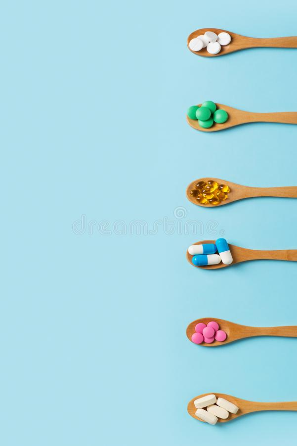 Set of colorful pills and tablets in spoon on blue background royalty free stock photo