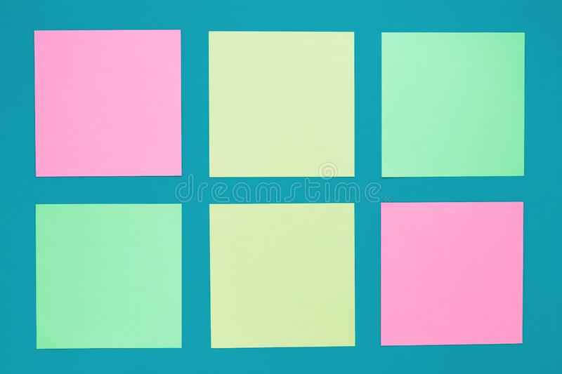 Set of colorful sticky notes on turquoise background. Multicolored stickers with copy spaces on blue board. Blank stickers, blank royalty free stock photo