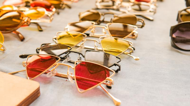 Set of colorful sunglasses for sale in a store. Different sunglasses on light coloured background stock images