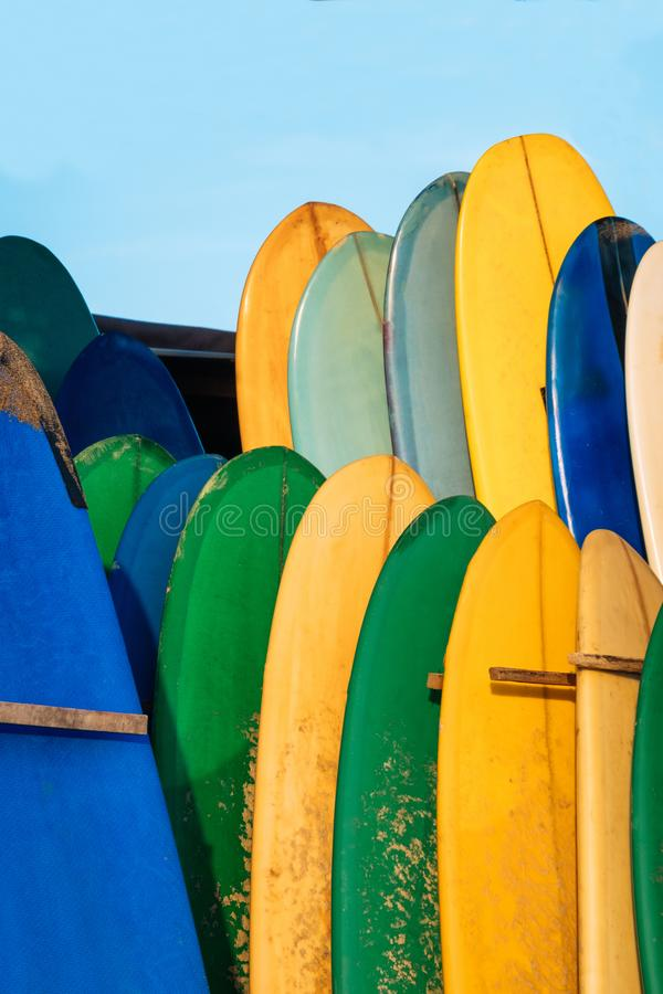 Set of colorful surfboard for rent on the beach. Multicolored surf boards different sizes and colors surfing boards on. Stand, surfboards rental place royalty free stock photos