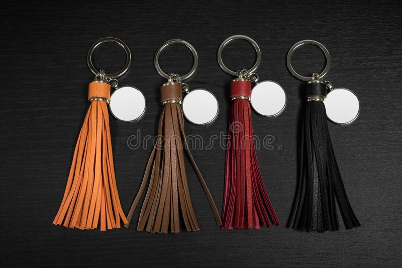 A set of Colorful Tassel key ring on black wooden background. Fashion leather key chain for decoration. A set of Colorful Tassel key ring on black wooden royalty free stock image