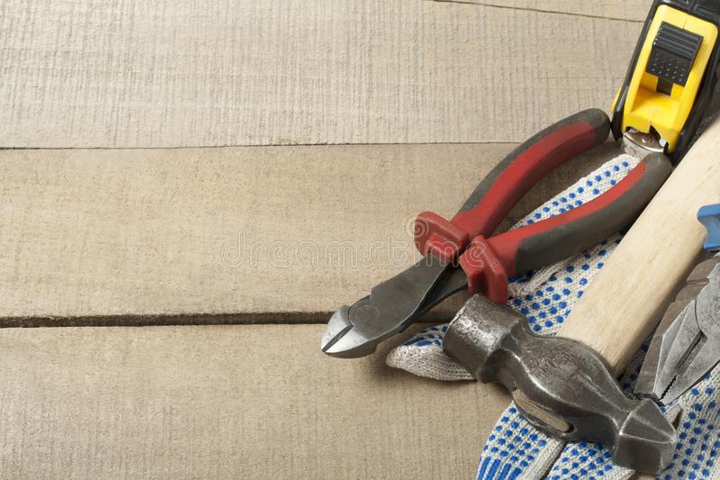 Construction tools and work gloves on wooden background .Copy space for text. stock photography