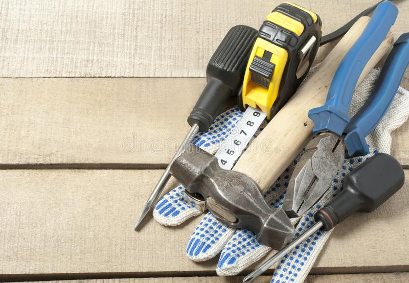 Construction tools and work gloves on wooden background .Copy space for text. stock image