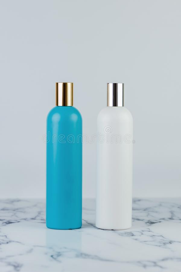 Set of cosmetic bottles, collection of two empty blue and white bottles of shampoo or lotion on white background on marble table.  royalty free stock photo