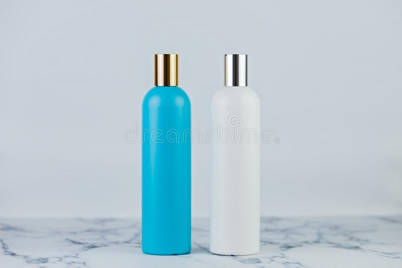Set of cosmetic bottles, collection of two empty blue and white bottles of shampoo or lotion on white background on marble table.  royalty free stock photos